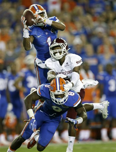 Florida defensive back Vernon Hargreaves III, top, intercepts a pass intended for New Mexico State wide receiver Tyrain Taylor, center, as defensive back Nick Washington (8) gets in on the play during the second half of an NCAA college football game, Saturday, Sept. 5, 2015, in Gainesville, Fla. Florida won 61-13. (AP Photo/John Raoux)